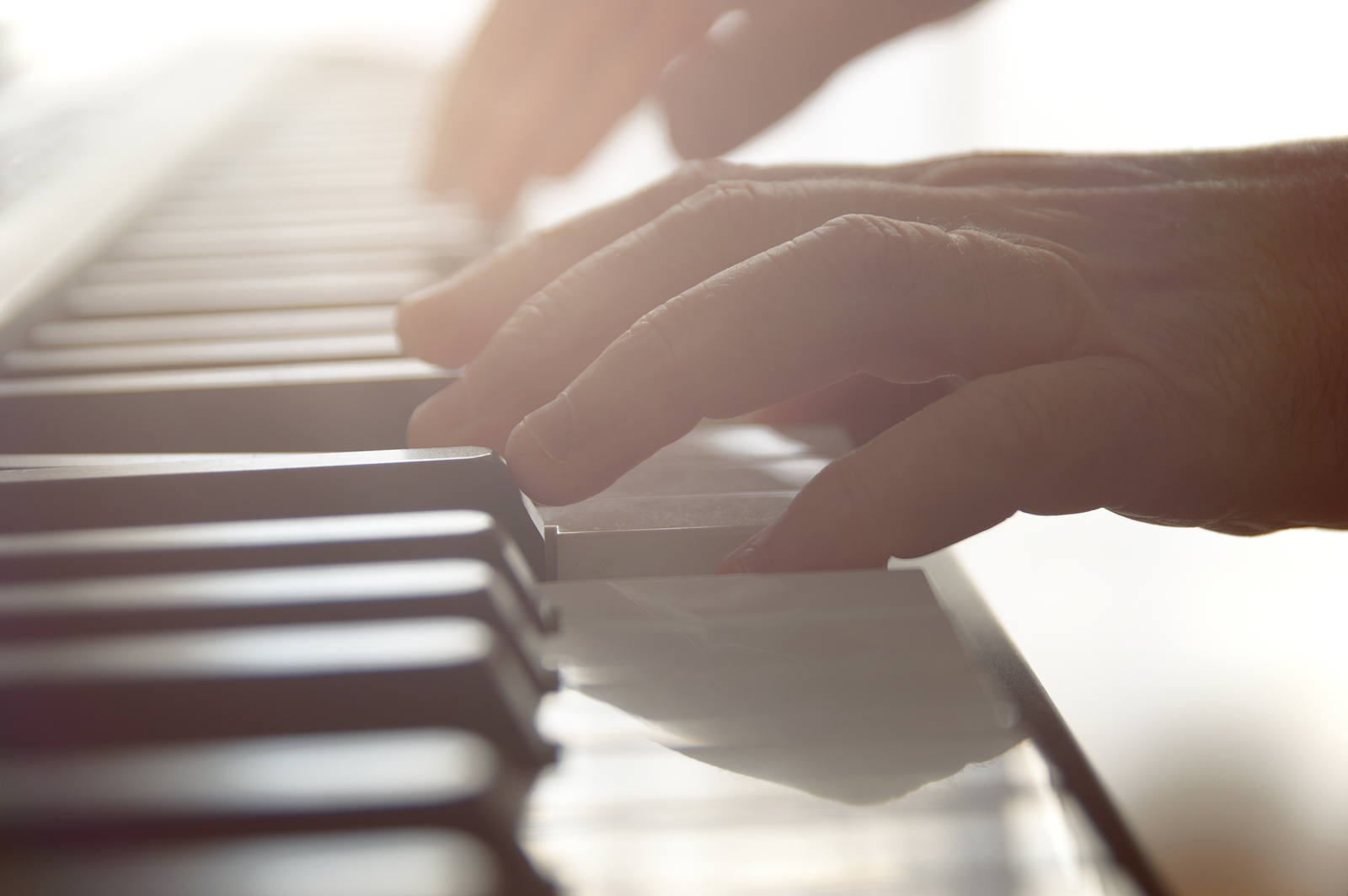 Hands playing a piano against a sunlight lighting at a music lesson in a class.